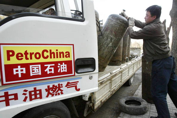 A PetroChina worker loads cannisters of