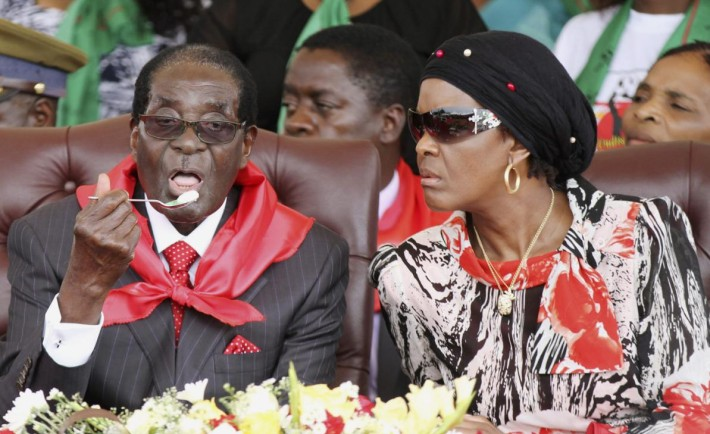 Grace Mugabe looks on next to her husband Zimbabwe President Robert Mugabe during his 91st birthday celebration in Victoria Falls February 28, 2015. Mugabe celebrated his 91st birthday with a lavish party by the spectacular Victoria Falls on Saturday, prompting many Zimbabweans to question once again when he would leave office and who would succeed him. Thousands of supporters were expected to attend the $1 million birthday celebration on a golf course near the waterfalls, organised by his ZANU-PF party. His party has said the money was raised from individual and company donations. REUTERS/Philimon Bulawayo (ZIMBABWE - Tags: POLITICS)